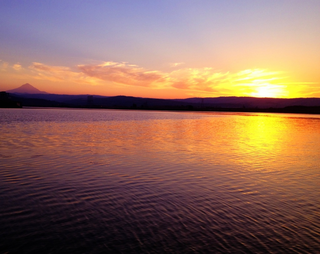 The sun sets over the Columbia River. Mt. Hood is visible in the distance.